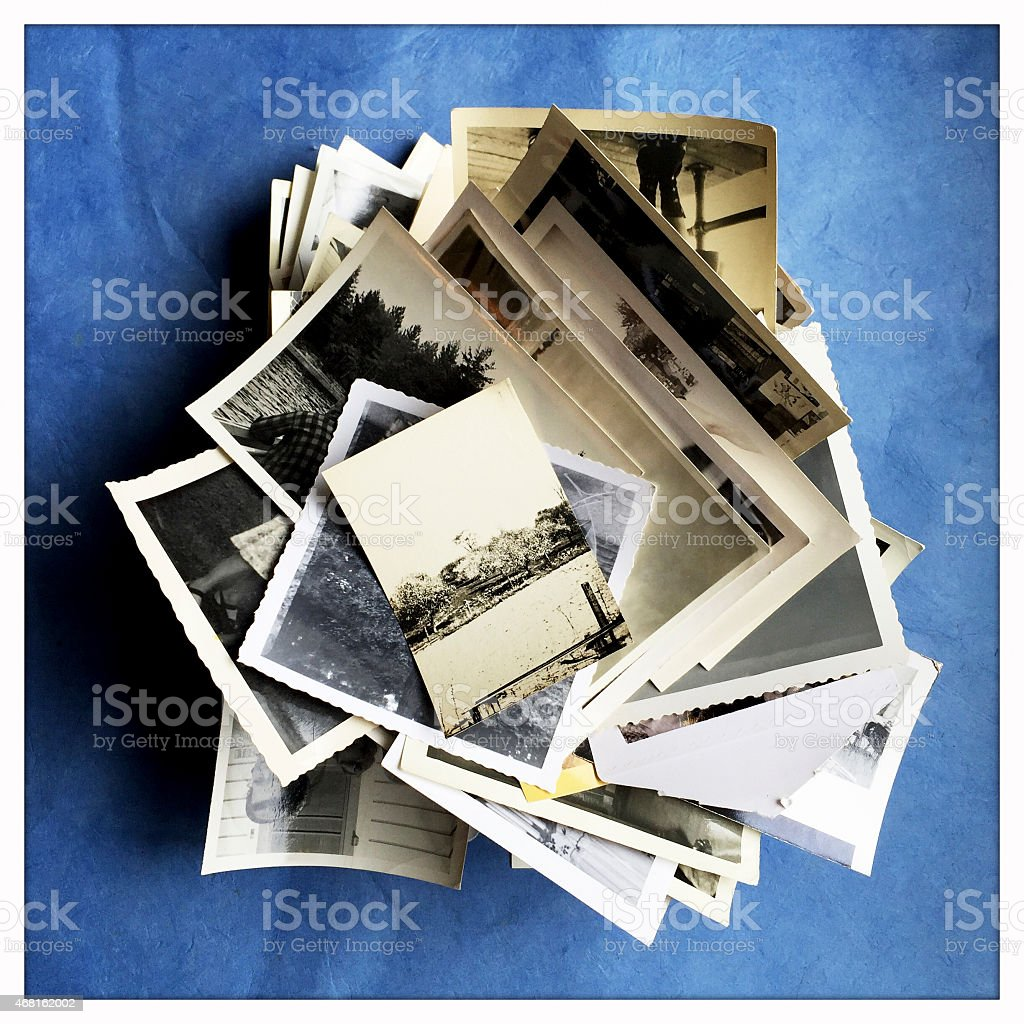 Old Photographs in a Pile on Blue Background stock photo
