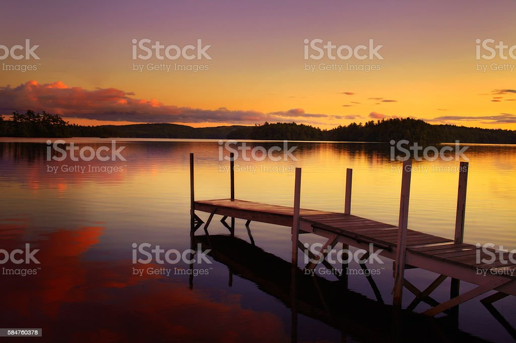 old pier in a lake at the sunset in maine stock photo