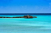 Old pier on bright blue water