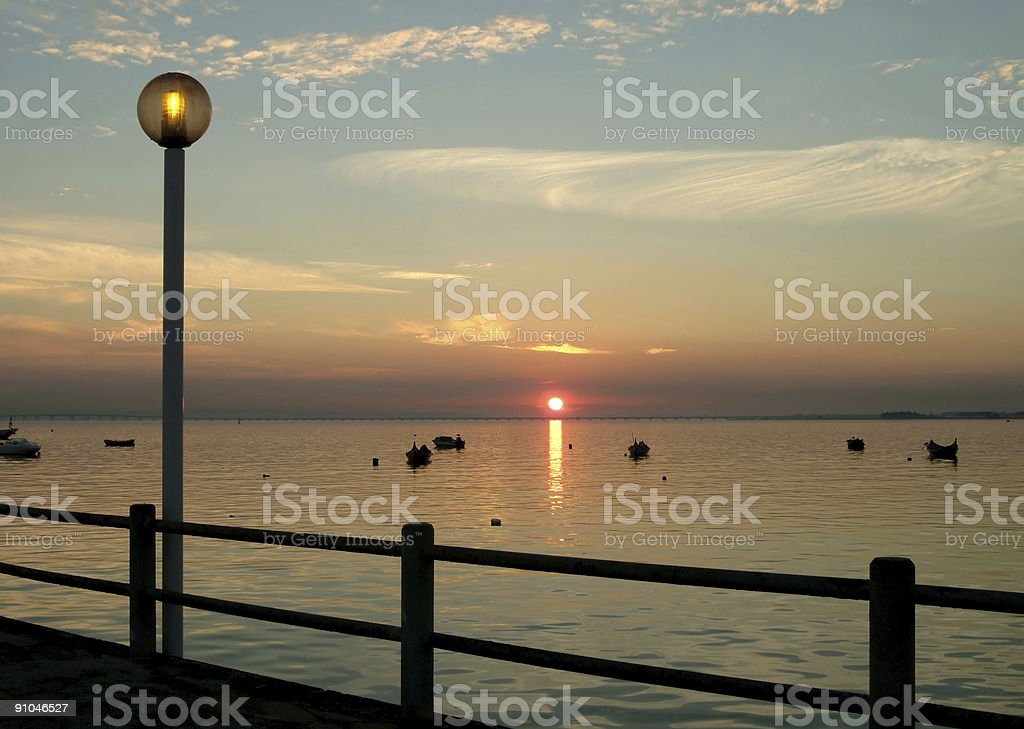 Old pier with lamp and boats at sunset royalty-free stock photo