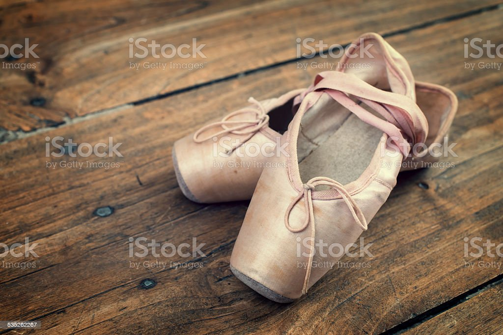 Old pink ballet shoes on a wooden floor, vintage process stock photo