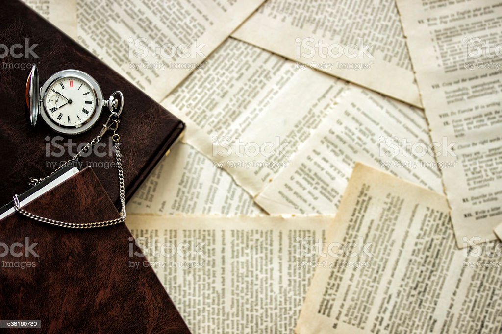 Old pocket watch and a book lying on the table stock photo