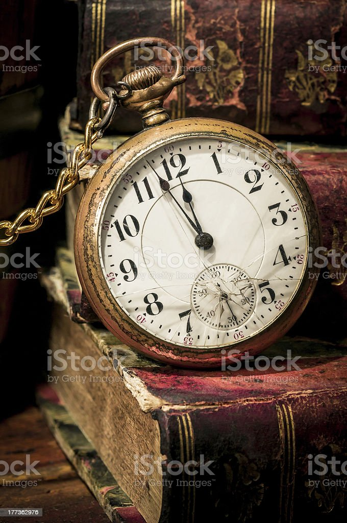 Old pocket watch and books in Low-key royalty-free stock photo