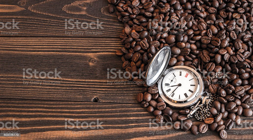 Old pocket watch lying on the coffee beans stock photo