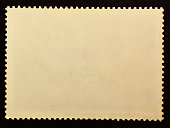 Old posted stamp reverse  side isolated on black background