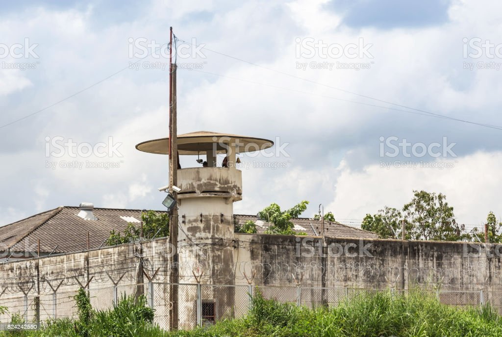 old prison guard tower or watchtower with barbed wire fence stock photo