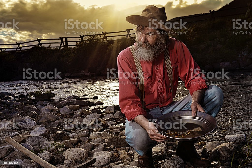 Old Prospector Panning For Gold In A Western Sunset stock photo