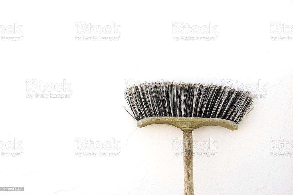 Old Pushbroom On Whitewashed Wall stock photo