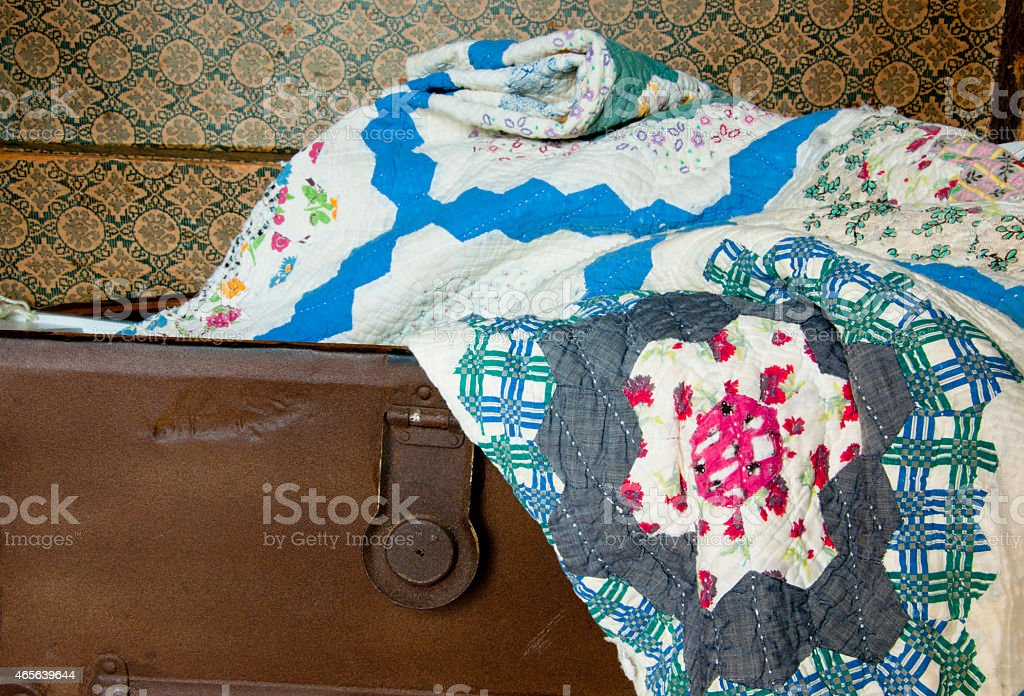 Old quilt lays in an antique trunk. stock photo