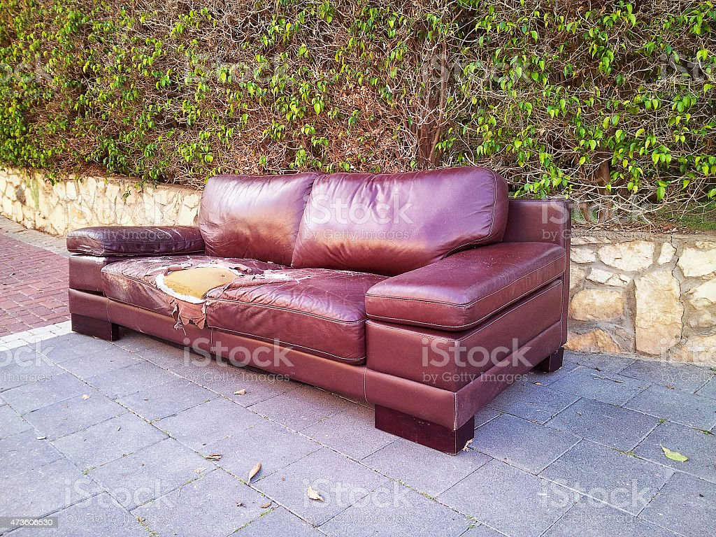 Old ragged leather sofa on a street stock photo