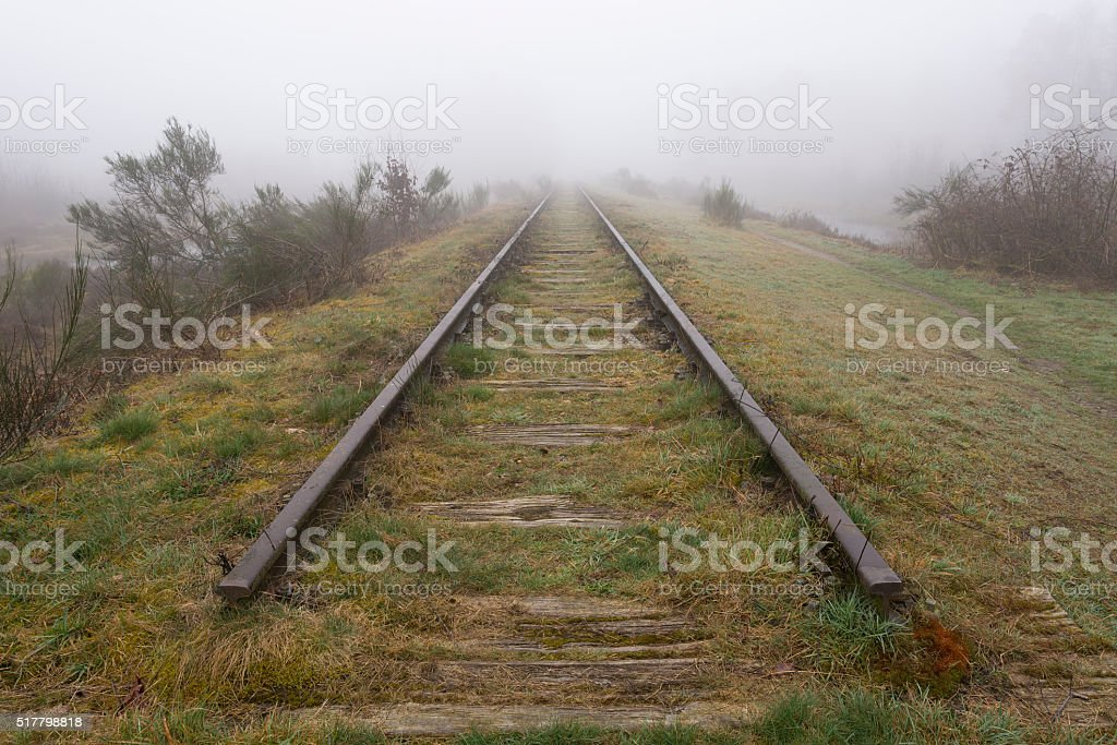 Old railway line shrouded in the fog stock photo