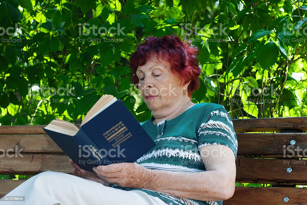 Old reading woman stock photo