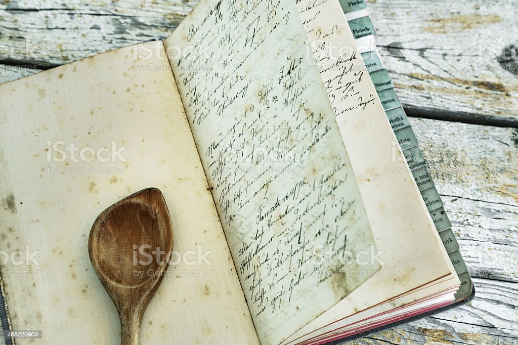 Old recipe book with wooden spoon stock photo