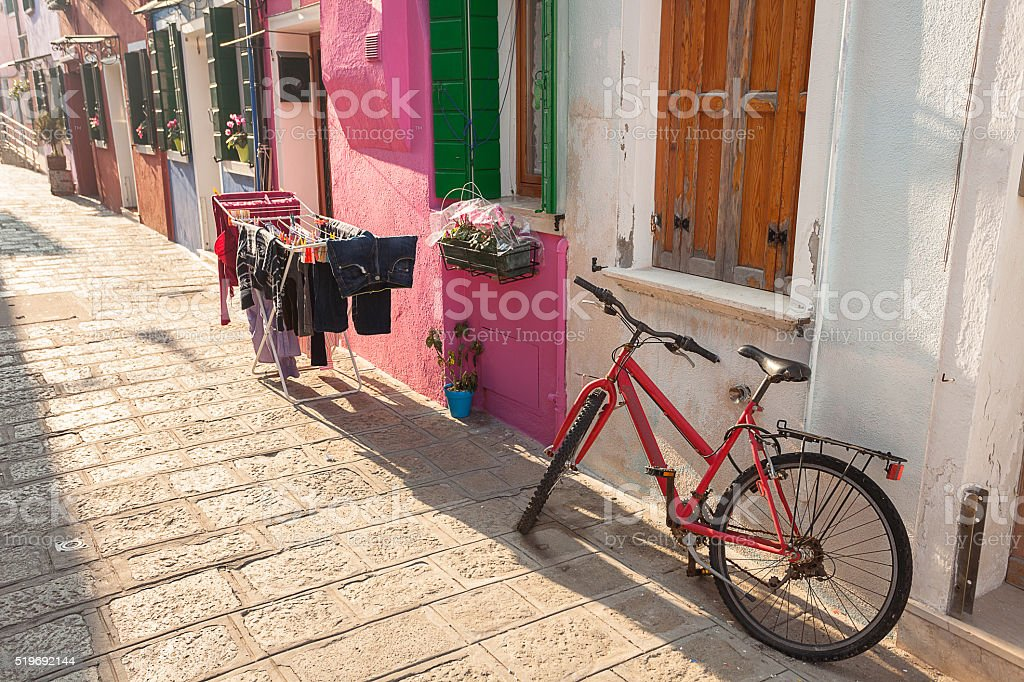 old red bicycle parked long an external wall in Burano stock photo