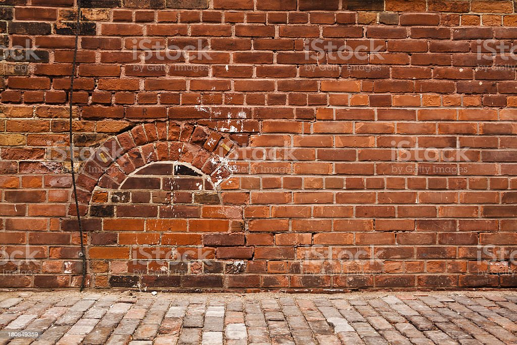 Old red brick wall with a bricked up door stock photo