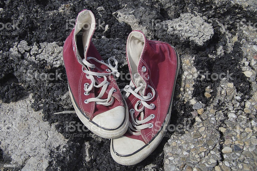 Old Red Canvas Shoes - Asphalt Background stock photo
