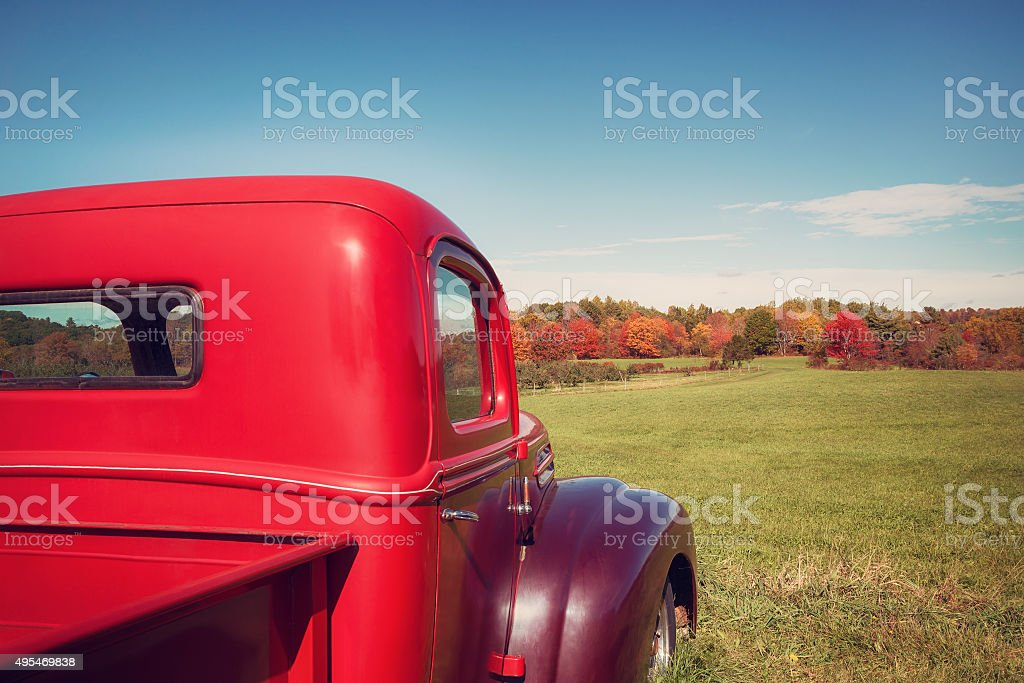 Old red farm truck against autumn landscape stock photo