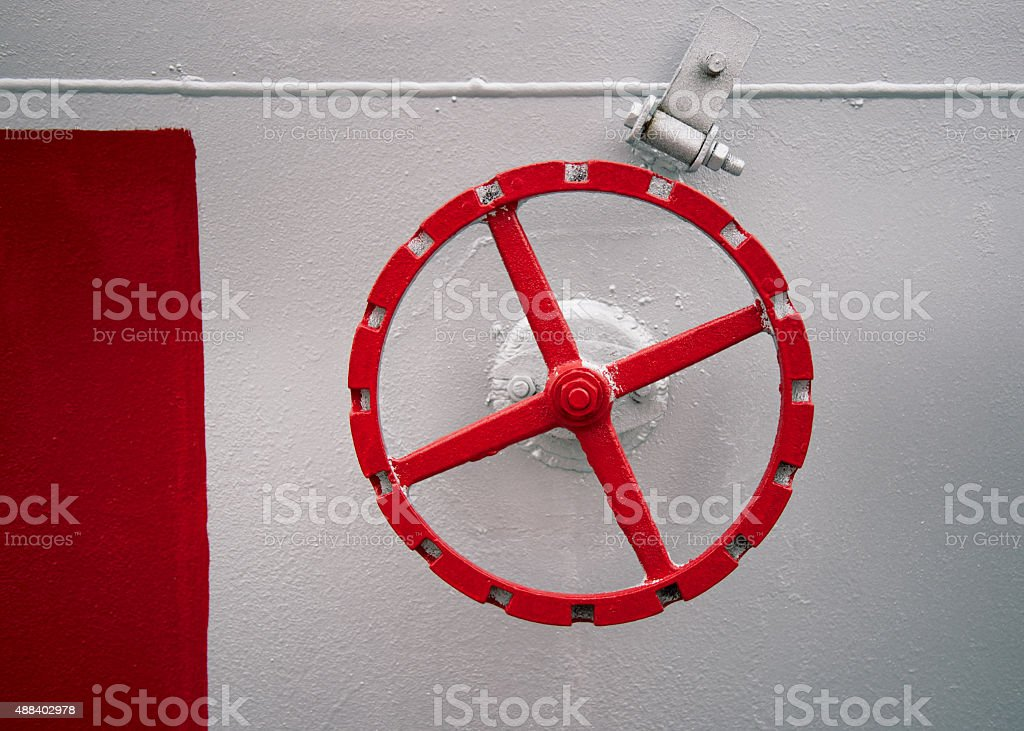 old red hand wheel on the wall of tank stock photo