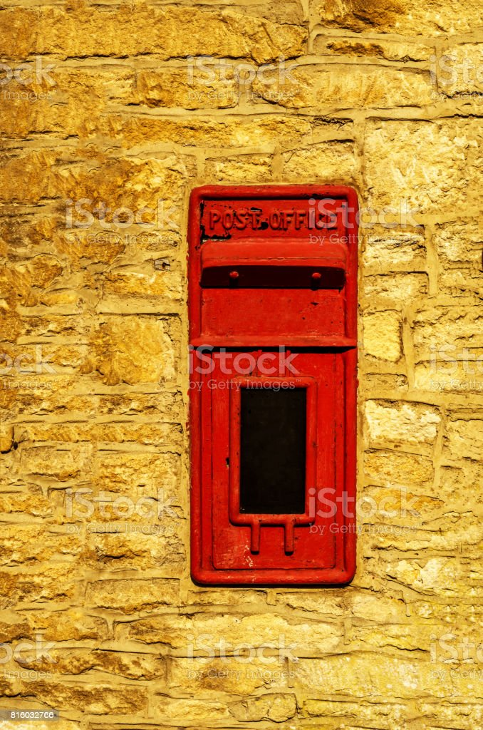 Old red letterbox in the wall, traditional way of delivering letters to the post office stock photo