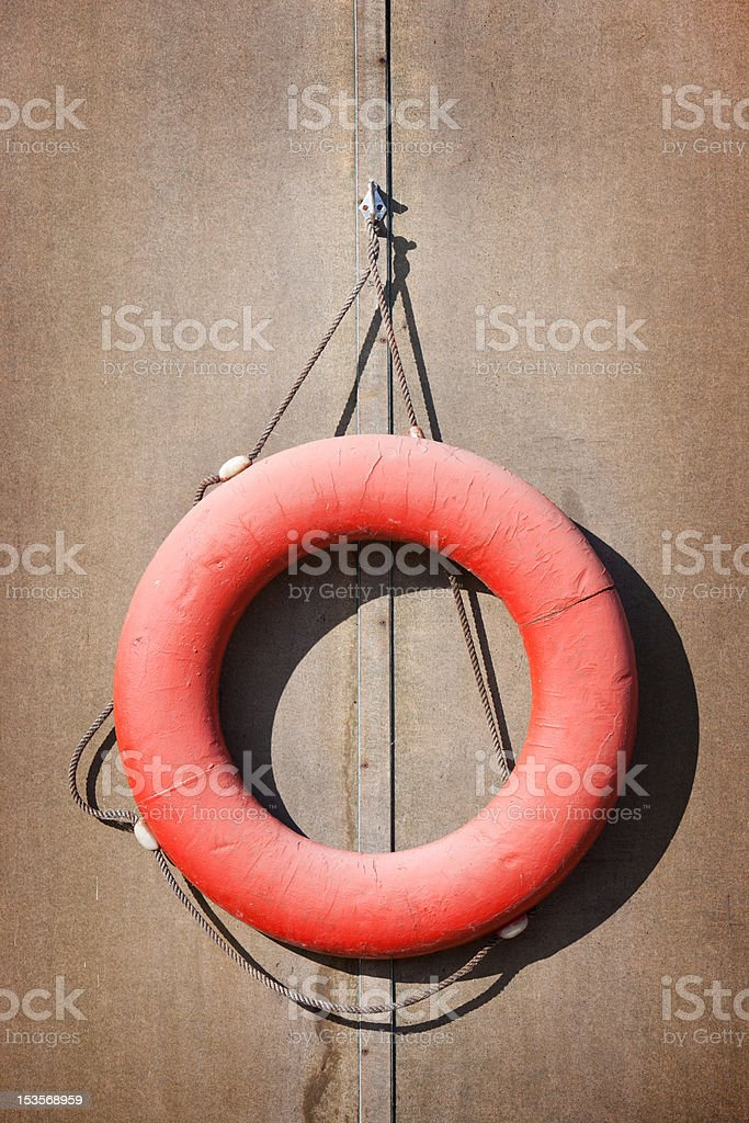 Old red lifebuoy on the wall stock photo