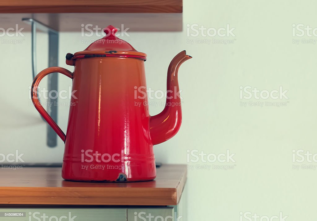 Old red teapot in interior, stock photo