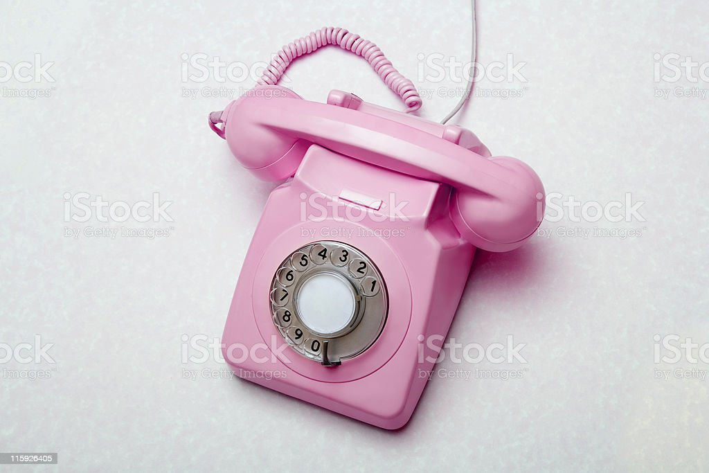 Old retro pink telephone on grey background royalty-free stock photo