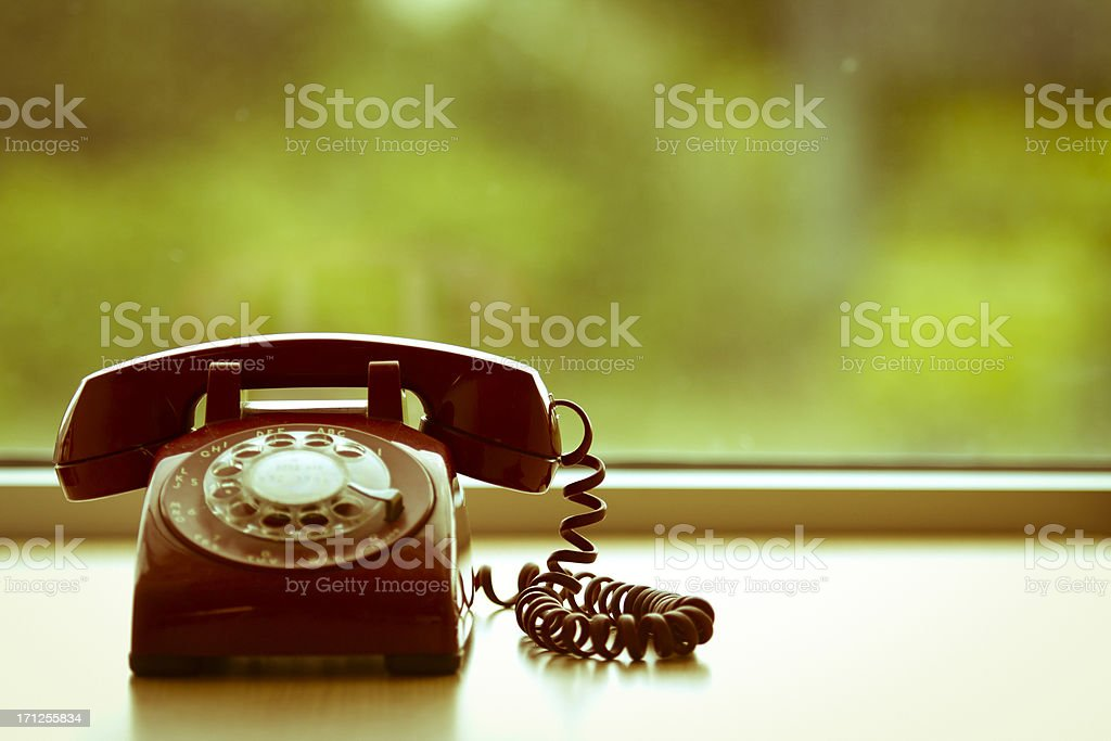 Old retro red rotary phone on a desk royalty-free stock photo