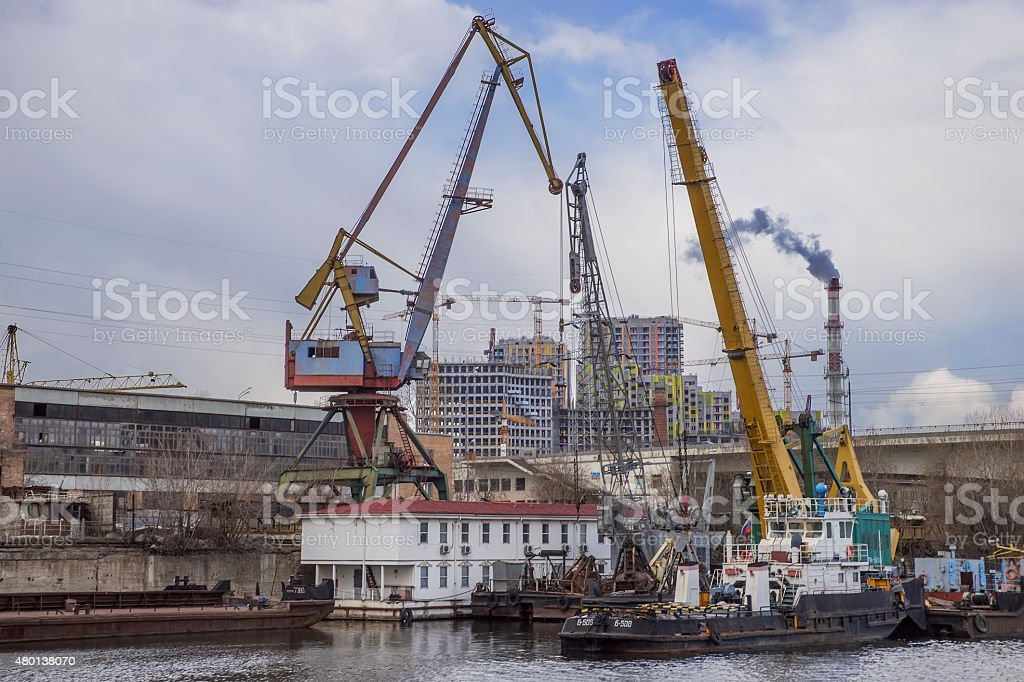 Old river barge crane on the background unfinished buildings. stock photo