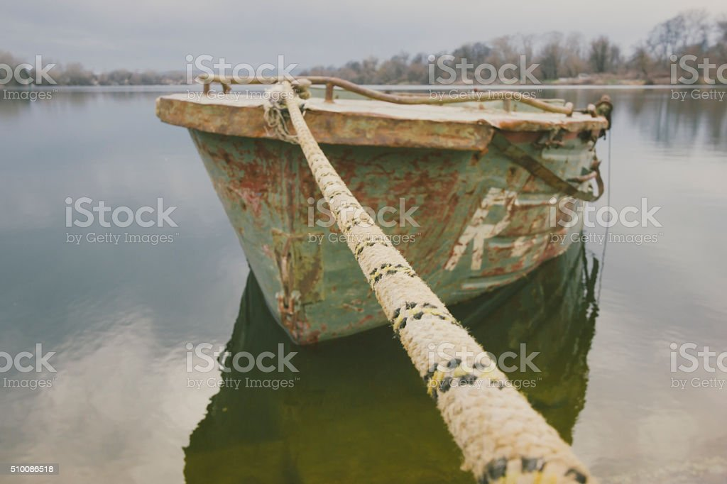 Old river boat tied with rope stock photo