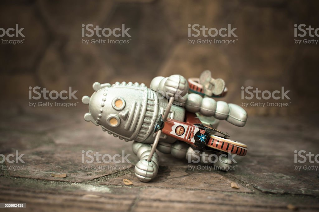 Old robot toy lost energy. stock photo