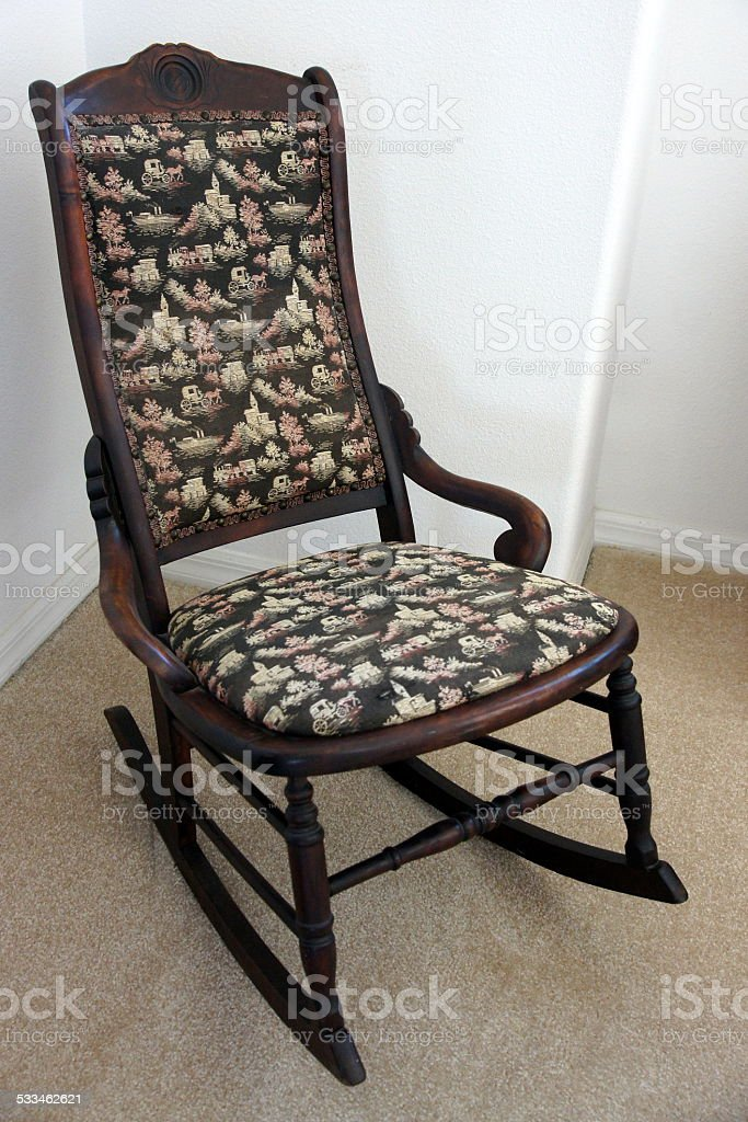 Old rocking chair sitting in a corner stock photo
