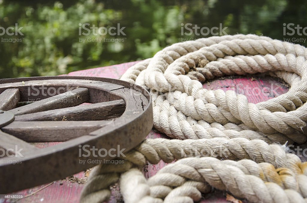 Old rolled ropes and a rusty wheel on a boat stock photo