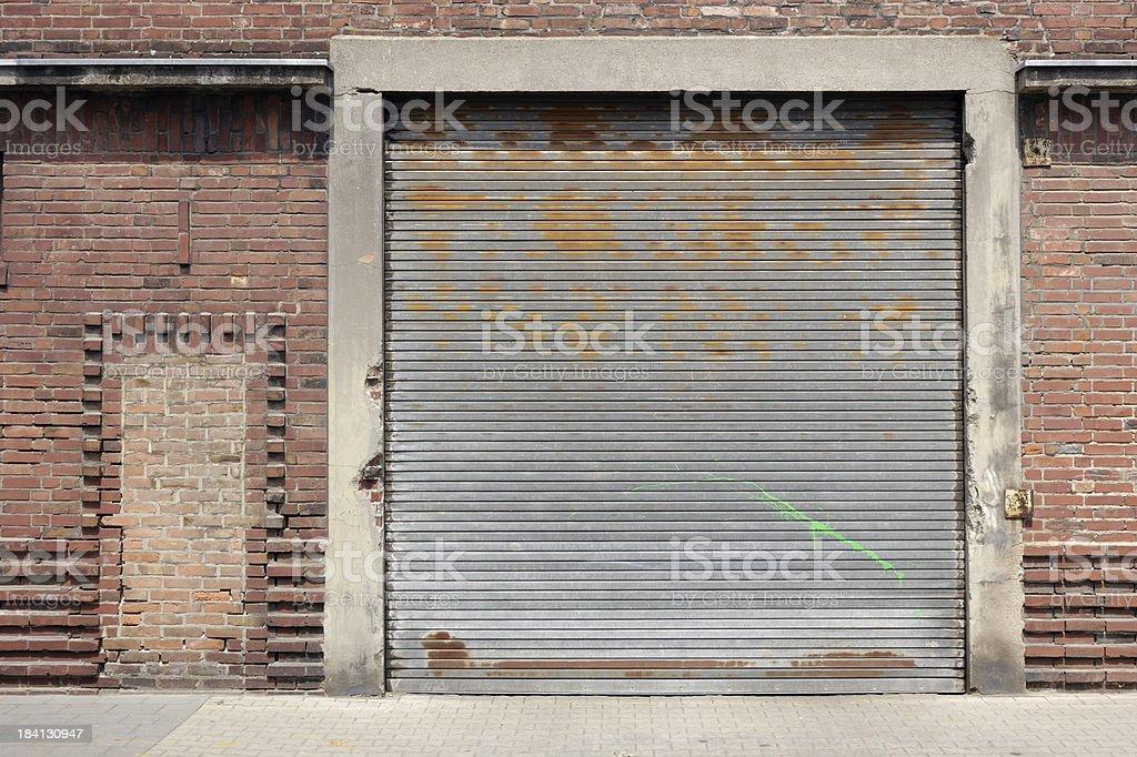 Old rolling garage door and brick wall stock photo