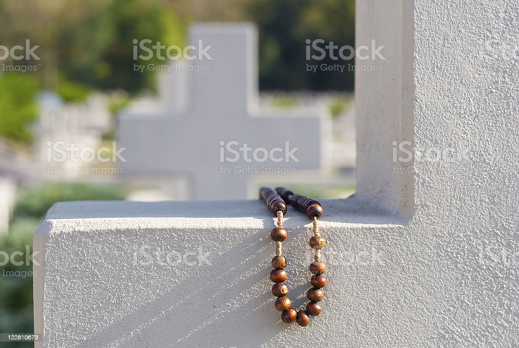 Old rosary on cemetery cross royalty-free stock photo