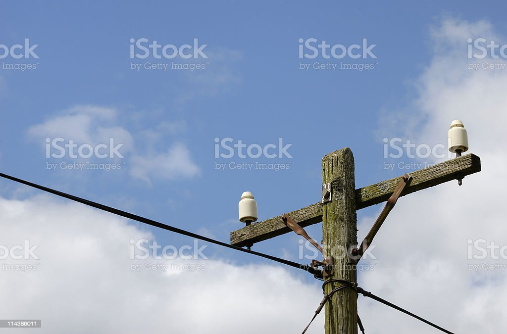Old rotting telephone pole with porcelain insulators and rusty brackets royalty-free stock photo