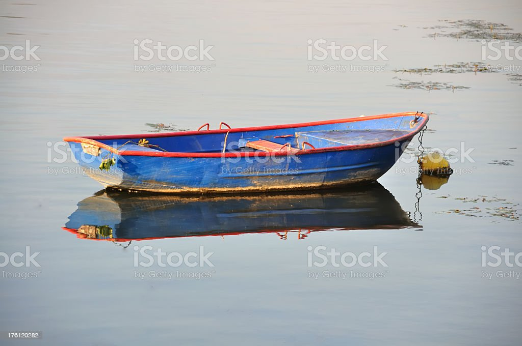 Old row boat in blue and red in shallow water royalty-free stock photo