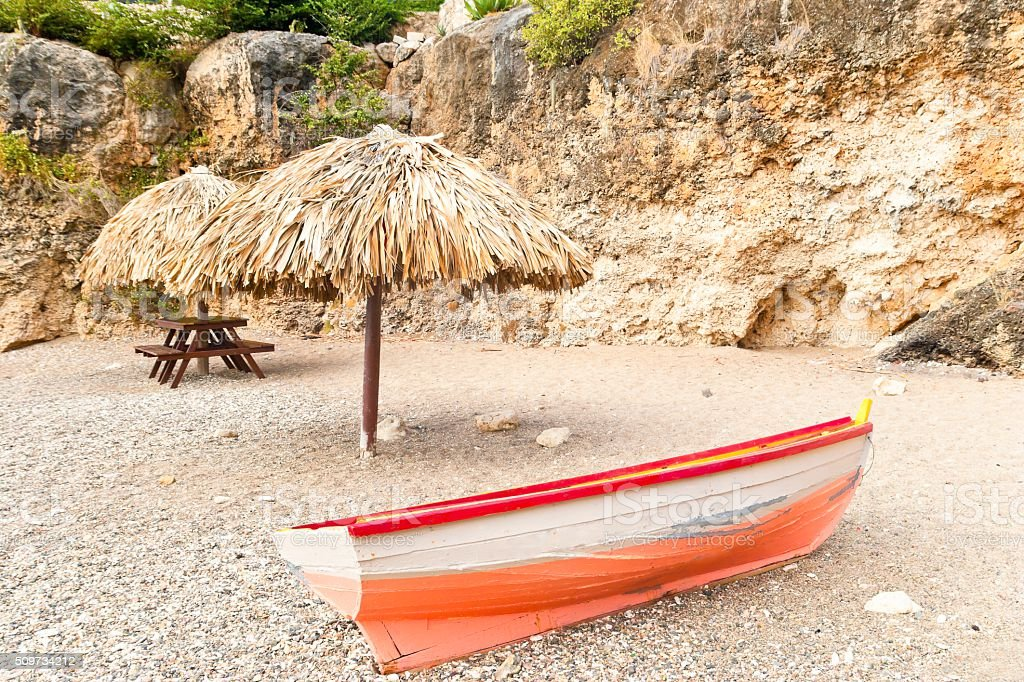 Old row boat on a rocky beach stock photo