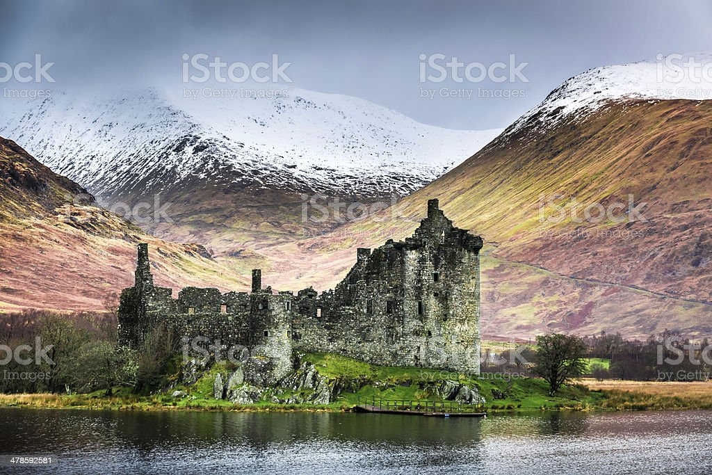 Old ruined castle on the background of snowy mountains stock photo