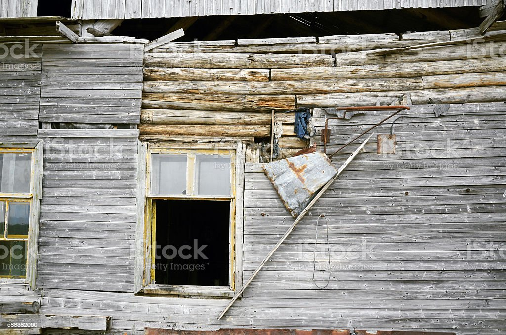 Old ruined wooden logs plank residential building, broken wall glasses stock photo