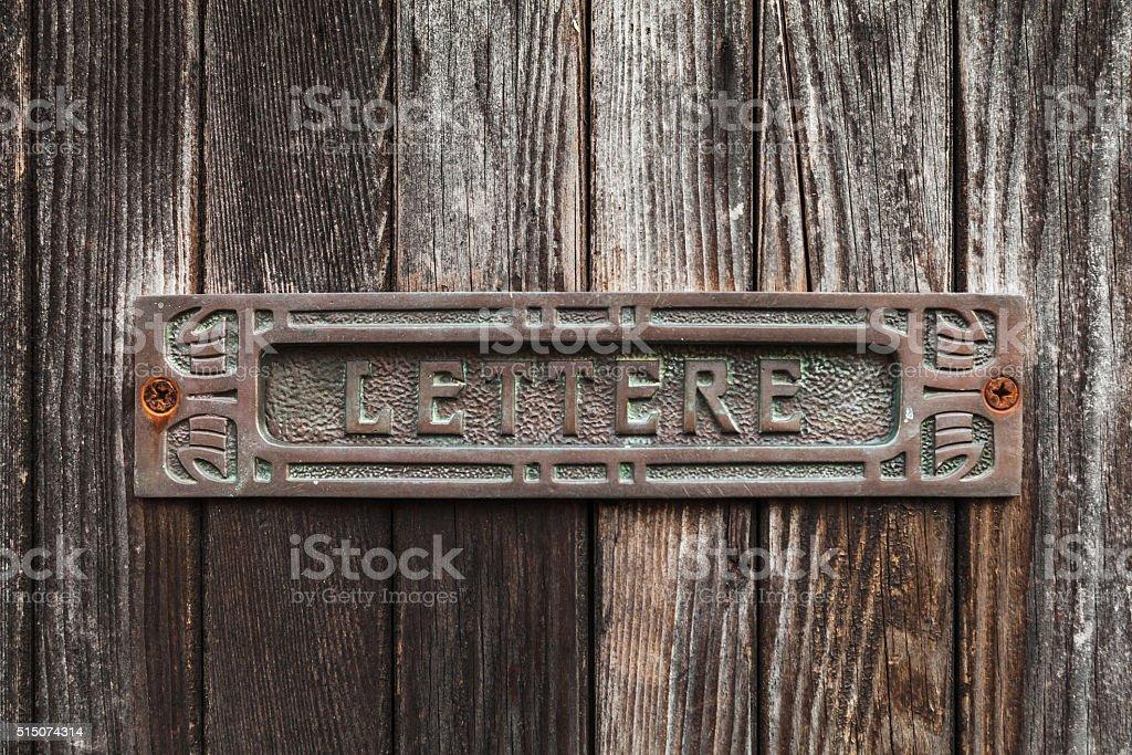 Old rusted mailbox in dark brown wooden door stock photo