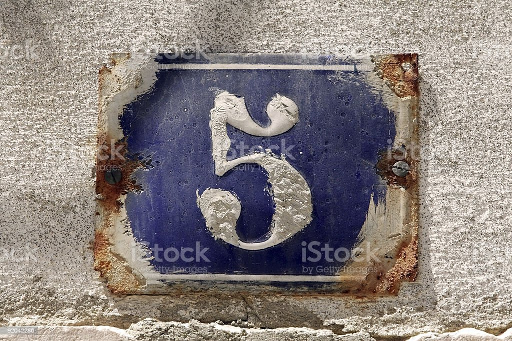 Old rusted number 5 house number over blue on a gray wall stock photo