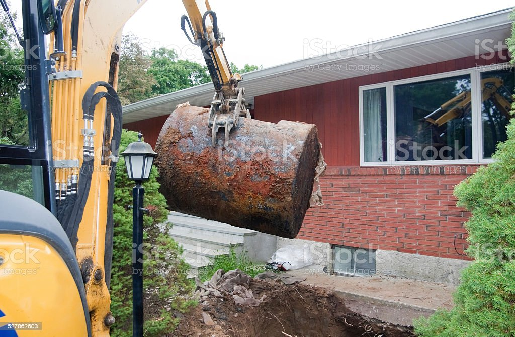 old rusted oil tank being removed from ground stock photo