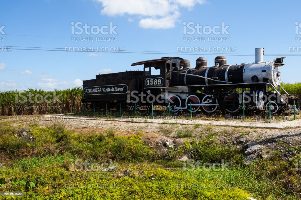 Old rusted steam in front of a sugar cane field stock photo