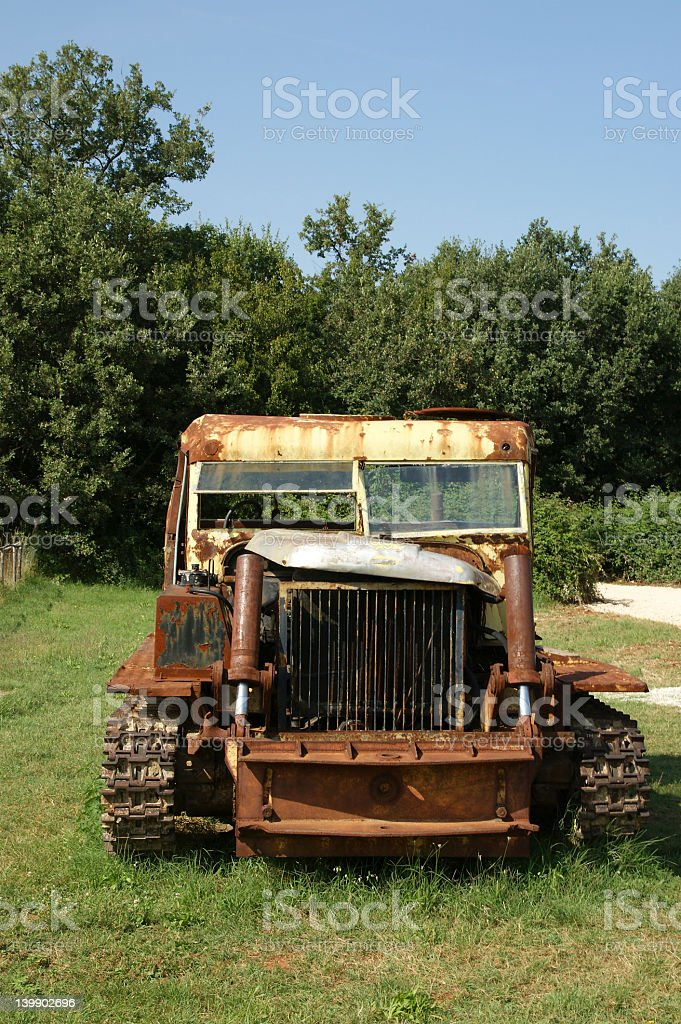 Old rusted tractor in a summer field royalty-free stock photo