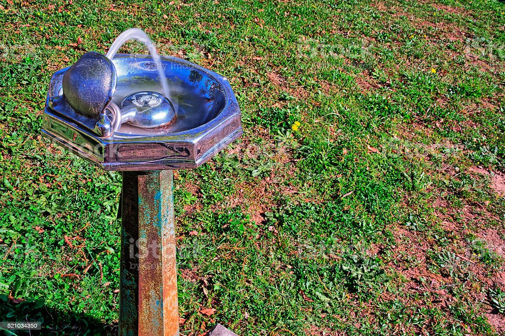 Old, rustic, water fountain with a grassy background stock photo