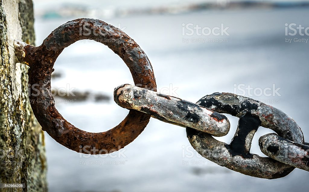 Old rusty anchor iron ship chain in sea port. stock photo