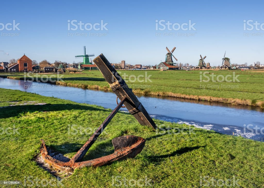 Old rusty anchor on green grass and windmills background landscape in Zaanse Schans, Amsterdam stock photo