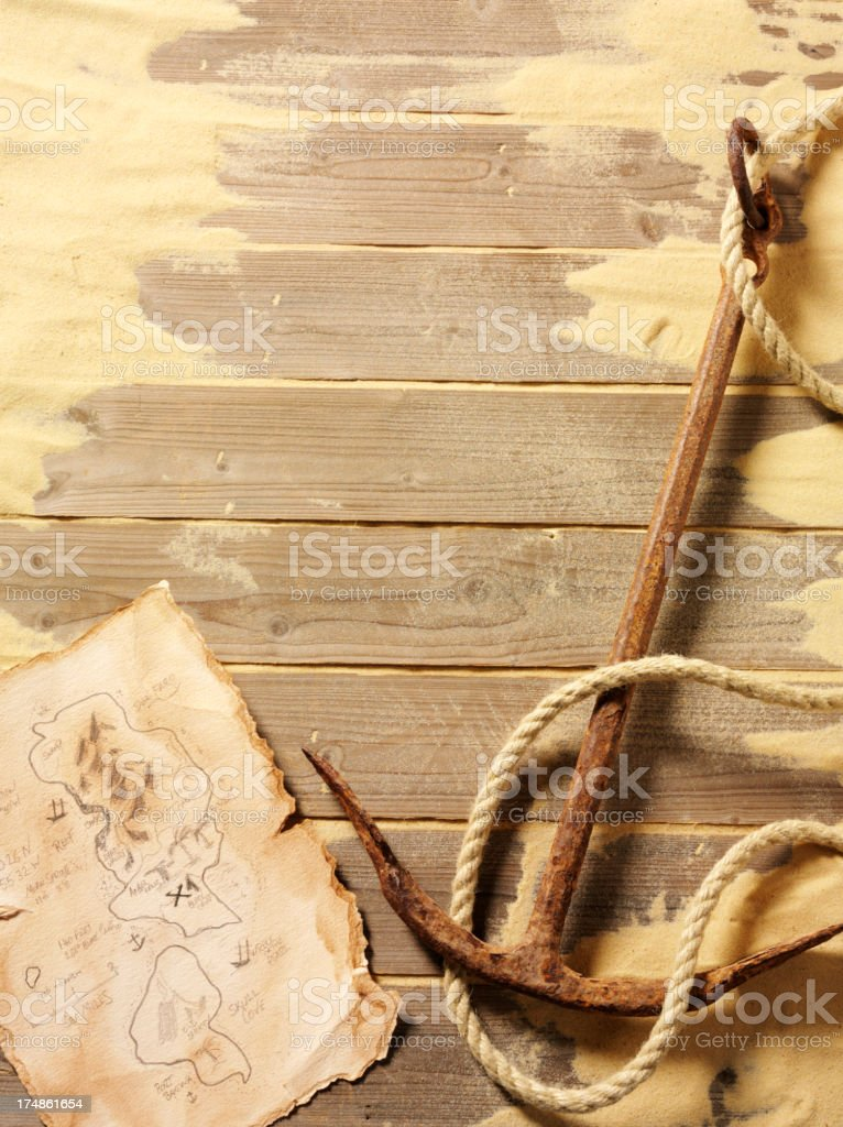 Old Rusty Anchor on Wooden Decking with Sand stock photo