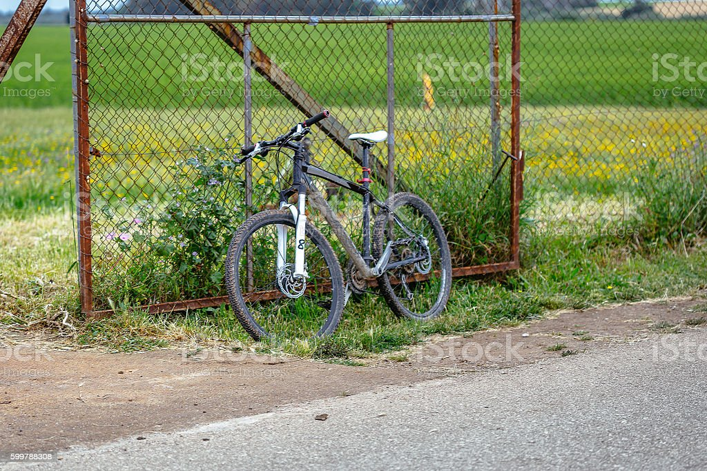 Old rusty Bicycle against fence in countryside foto royalty-free