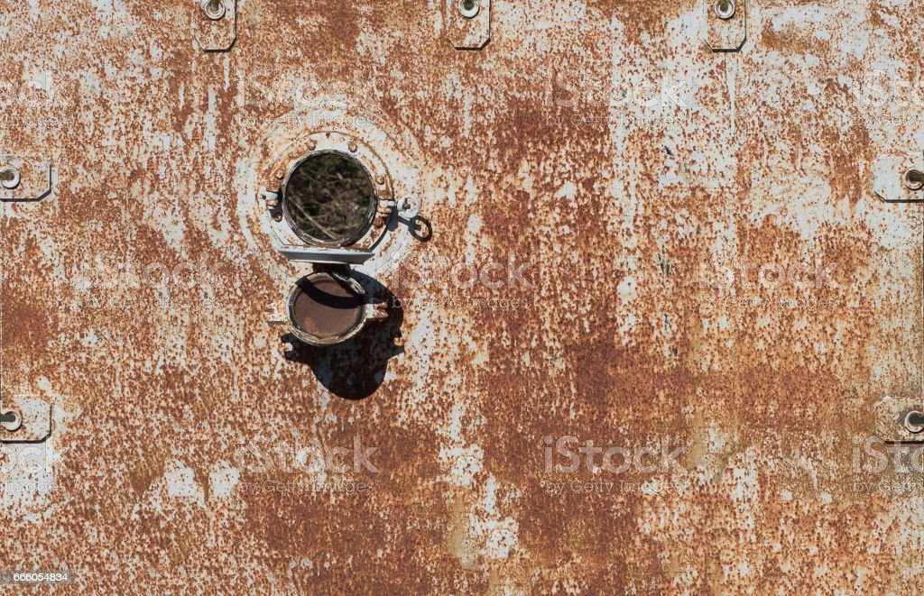 Old rusty circular window on an old ship stock photo
